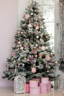 ピンク色とその下に贈り物とピンクのボックスで飾られた大きな美しいクリスマスツリー
