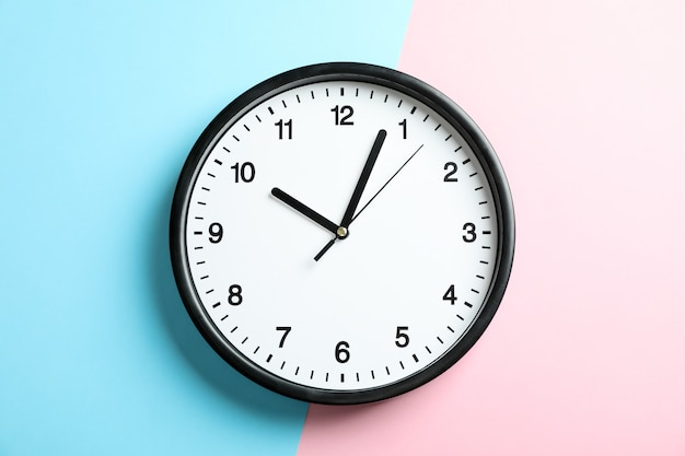Big beautiful office clock on two tone solid color pink and light blue