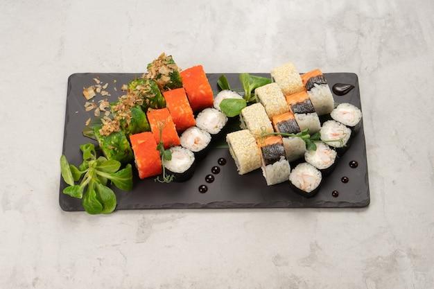Big beautiful set of different types of sushi maki on a black rectangular stone slate plate
