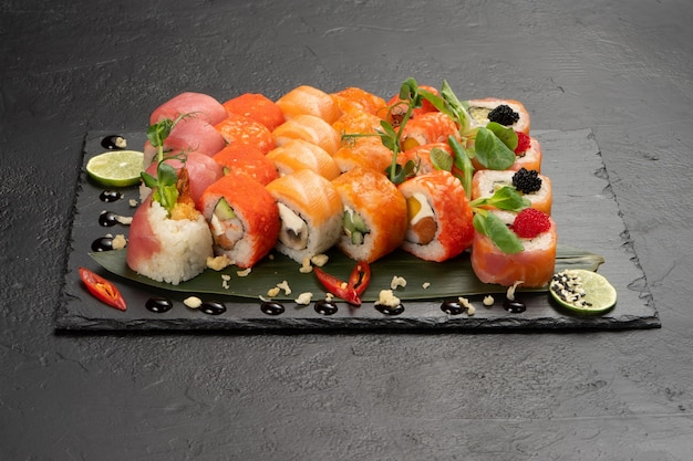Big beautiful set of different types of sushi maki on a black rectangular stone slate plate.
