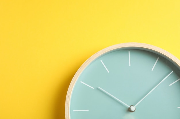 Big beautiful stylish clock on yellow, space for text