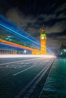 Big ben at night with the lights of the cars in london city, uk.