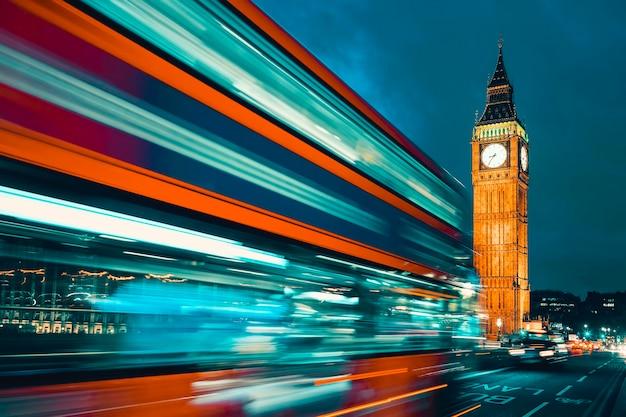 Биг бен, один из самых ярких символов лондона и англии, изображенный ночью вместе с огнями проезжающих мимо автомобилей.