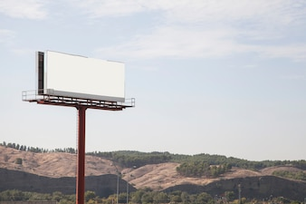 Big billboard advertising sign with mountains and sky in the background