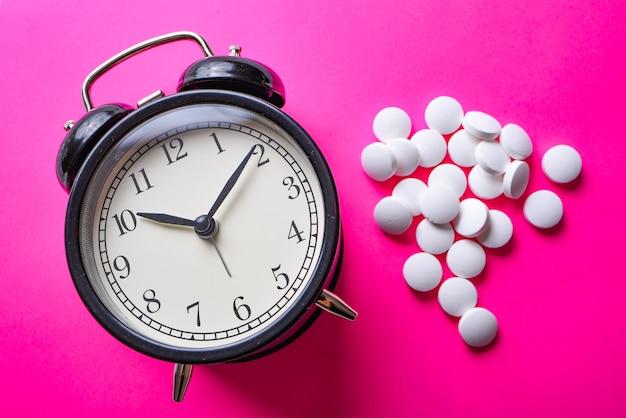 大きな黒い目覚まし時計と明るいピンクの多くの白い錠剤
