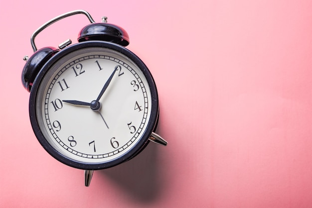 Big black alarm clock on a bright pink background. lost time or good morning concept.