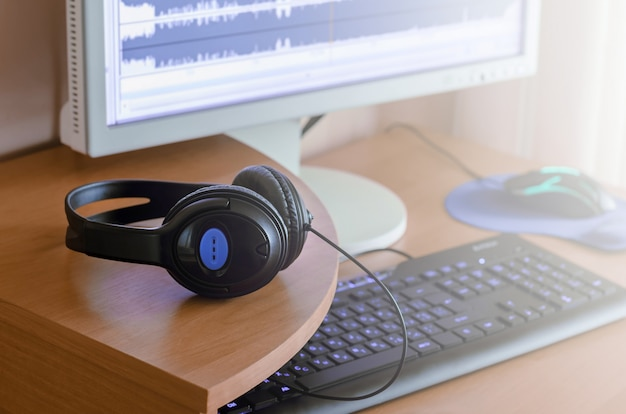 Big black headphones lie on the wooden desktop of the sound designer