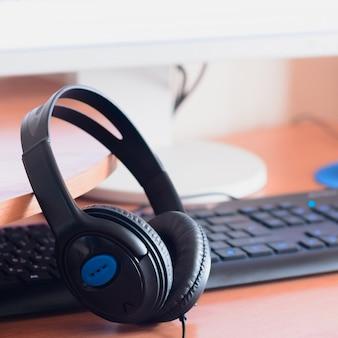 Big black headphones lie  wooden desktop of the sound er