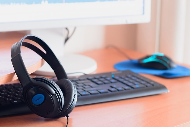 Big black headphones lie  wooden desktop of the sound