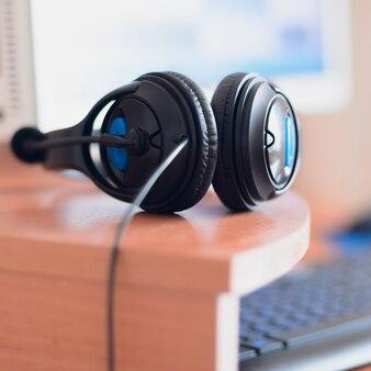 Big black headphones lie on the wooden desktop