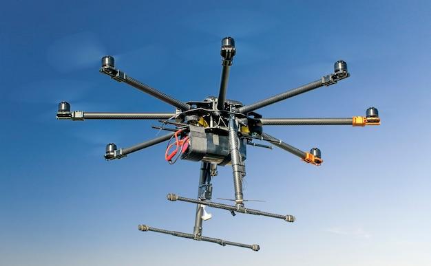 Большой черный самодельный мощный гексакоптер на фоне голубого неба, крупным планом.