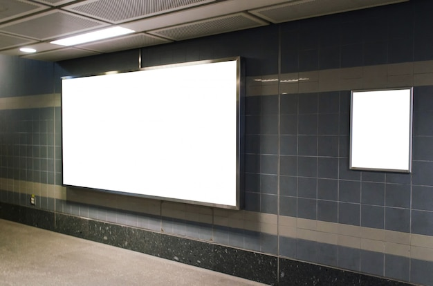 Big blank advertising billboard on wall with copy space in subway train station or airport