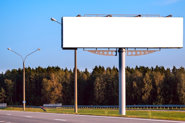 森に対する高速道路に沿って大きな空白の看板のモックアップ