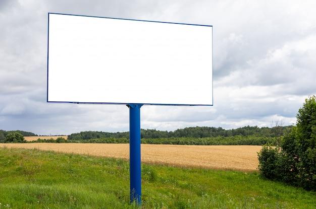 Big blank billboard mockup along highway against field