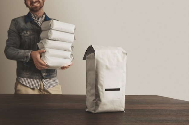 Big blank bulky sealed package with product isolated on wooden table in front of unfocused smiling