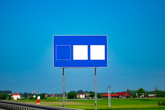 Big blank highway road sign with gradient blue sky.