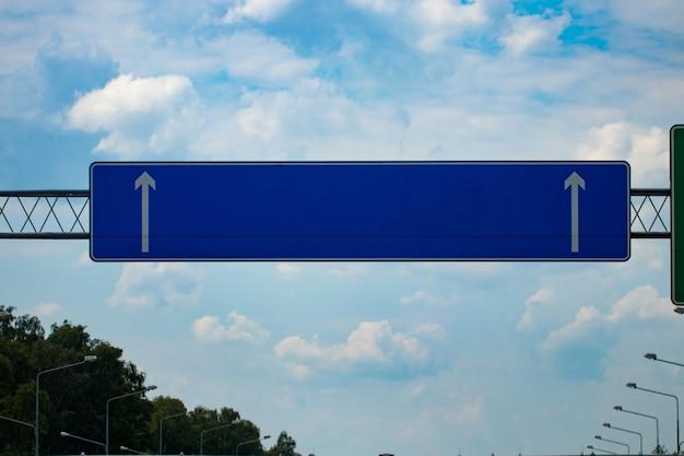 Большой пустой дорожный знак шоссе с градиентным голубым небом.