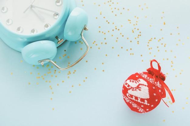 大きな青い目覚まし時計が横たわっていて、23時間55分を示す表面と、水色の表面に光沢のある紙吹雪の星が付いたクリスマスの赤いボール。上面図。