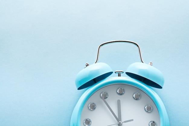 大きな青い目覚まし時計が横たわっていて、水色の表面に23時間55分を示しています。上面図。