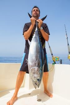 Большой улов синего тунца рыбака на лодке троллинг