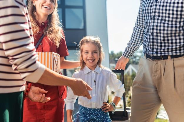 빅 보스. 그녀의 부모 근처에 서있는 동안 그녀의 얼굴에 미소를 유지하는 예쁜 아이