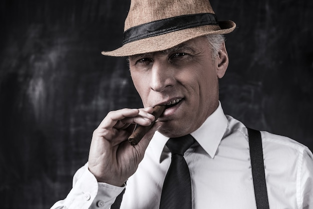 Big boss. serious senior man in hat and suspenders smoking cigar and looking at you while standing against dark background