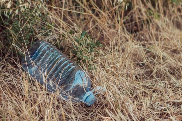 필드에 잔디 가운데 물 큰 병. 환경 플라스틱 오염 개념