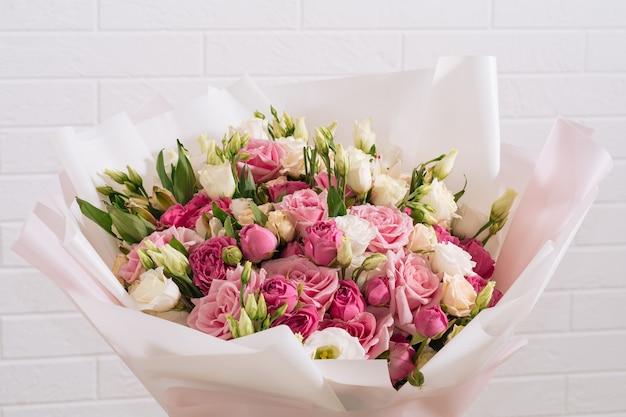 ピンクのパッケージで美しく明るいホワイトピンクのバラとトルコギキョウの大きな花束