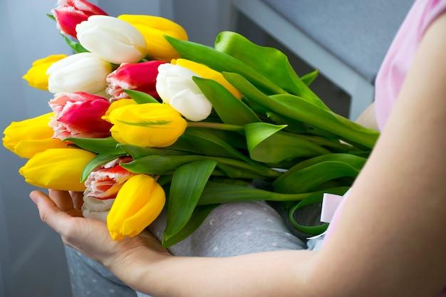 家庭服で女性の膝の上に美しい花のカラフルなチューリップの大きな花束