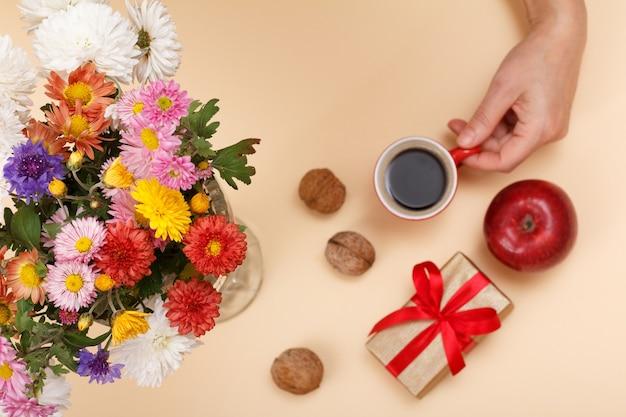 다채로운 꽃의 큰 꽃다발, 커피 한 잔과 선물 상자가 있는 여성 손, 베이지색 배경에 사과. 평면도. 필드의 얕은 깊이. 꽃에 초점.
