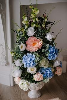Большой букет из свежих цветов, розовых, голубых гортензий, белых роз и зелени в вазе. свадебные цветы, букет невесты крупным планом. домашний декор на полу, винтажный стиль. предметы украшения.