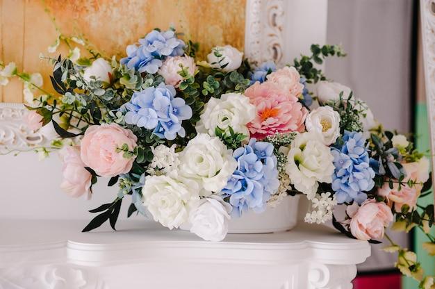 Большой букет из свежих цветов, розовых, голубых гортензий, белых роз и зелени в вазе. свадебные цветы, букет невесты крупным планом. домашний декор на столе, винтажном стиле. предметы украшения.