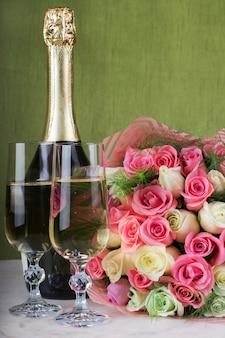 Большой букет роз обручальное кольцо в бокале шампанского и бутылка шампанского на мраморном столе