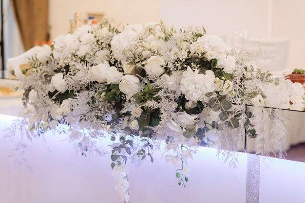 テーブルの上に白いバラとユーカリの大きな花束が立つ