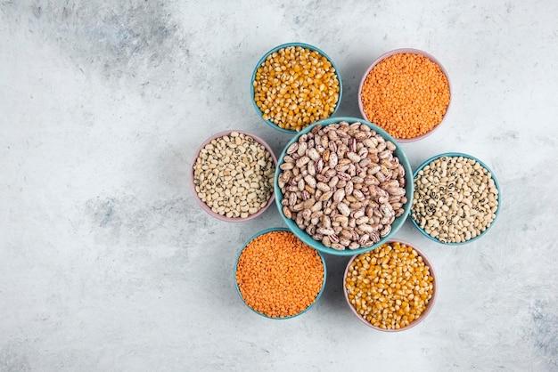 Grande ciotola di fagioli marroni intorno a vari fagioli e lenticchie crudi.