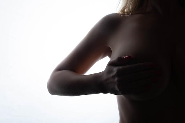 섹시한 여성의 큰 가슴은 흰색 바탕에 성형 교정 및 수술 개념 실루엣을 닫습니다.