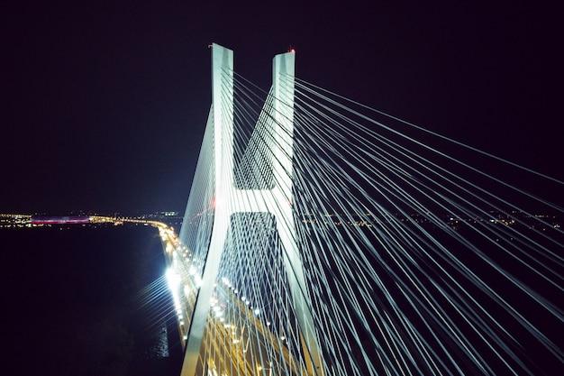 Большой мост ночью ярко светится с высоты птичьего полета, архитектура моста. кабели, вроцлав