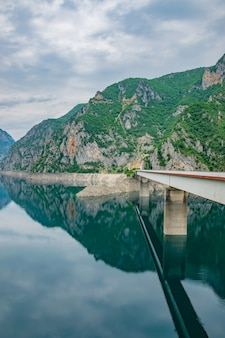The big bridge is crossed by a picturesque mountain lake.