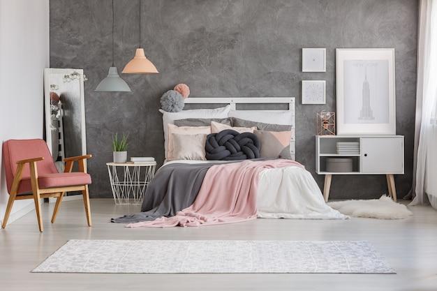 Большой яркий ковер с узорами, лежащий на полу в уютной комнате с кроватью