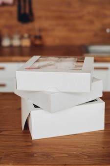흰색 찬장이 있는 크고 밝은 주방과 흰색 상자에 많은 달콤한 음식