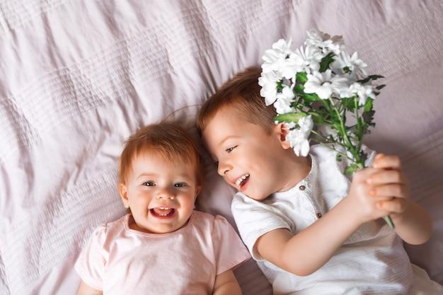 兄は妹、面白くて幸せな子供たちに花を贈ります
