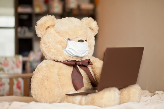 Big brown bear toy in medical mask sitting on the bed with digital tablet laptop notebook. online call friends or parents.