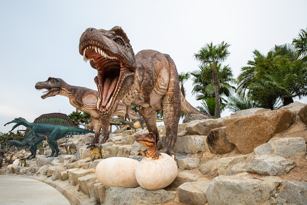 Big brown dinosaur statue on the rock in the park asia thailand