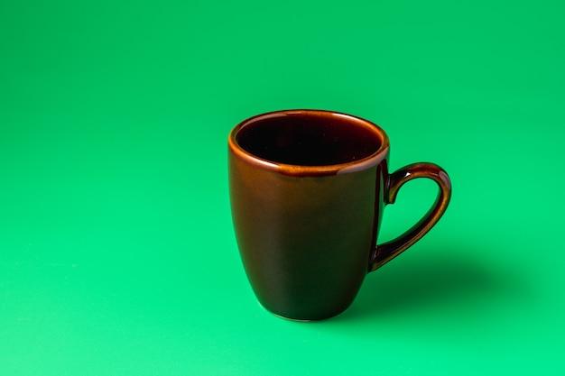 Big brown mug on green surface