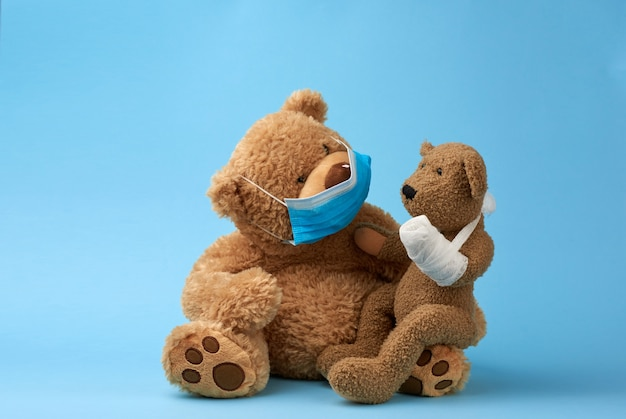 Big brown teddy bear sits in a medical mask, in his hands he holds a small toy