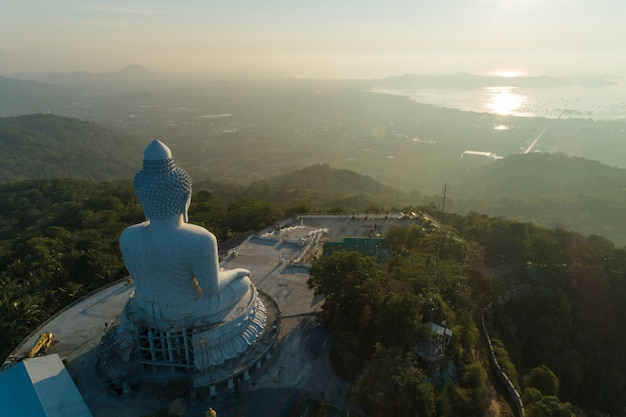 Big buddha over high mountain in phuket thailand aerial view drone shot in the morning.