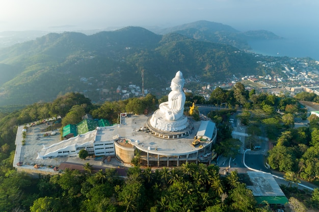 Big buddha over high mountain in phuket thailand aerial view drone shot.