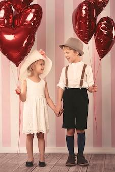 Милые дети держат большой букет воздушных шаров