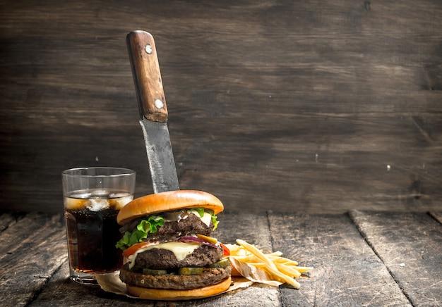 Большой бургер с колой и картофелем фри. на деревянном столе.