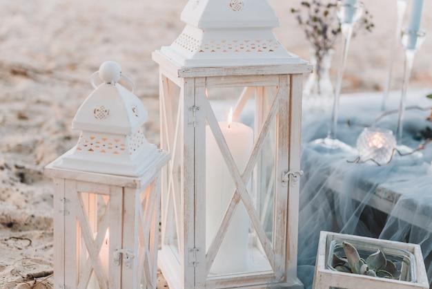 ビーチでの結婚式のための青いパステルカラーのエレガントなテーブルの横にある大きなキャンドル